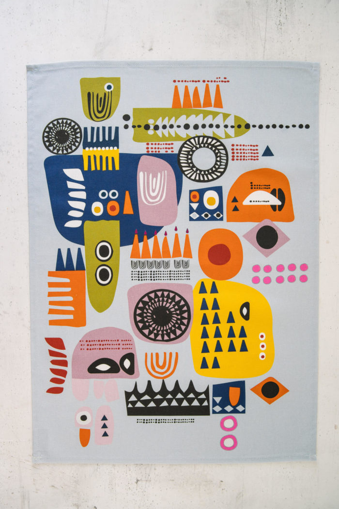 "The ""Shapes"" colourful tea towels are a Scandinavian influenced abstract, bold and contemporary design. The two contemporary tea towel designs have subtle differences, both with playful, colourful combinations of abstract patterns suggesting faces. Design 1 (seen here) has more yellow, while design 2 has more blue. You can match or mix and match these quirky tea towels with oven gloves  in the same design, for a full kitchen set. Features: Hanging loop 50cm x 70cm 100% cotton Wash at 40 degrees Made in Great Britain If you like this quirky design, you might also like to mix and match with the bright and bold ""Solstice"" tea towels, oven gloves and apron for a full kitchen set. Both designs are strongly influenced by Scandinavian folklore and design. All dyes used by Softer + Wild are water-based and very gentle and reflect a rustic, organic feel to their products – perfect for gifting and bring comfort, luxury and design to the table."