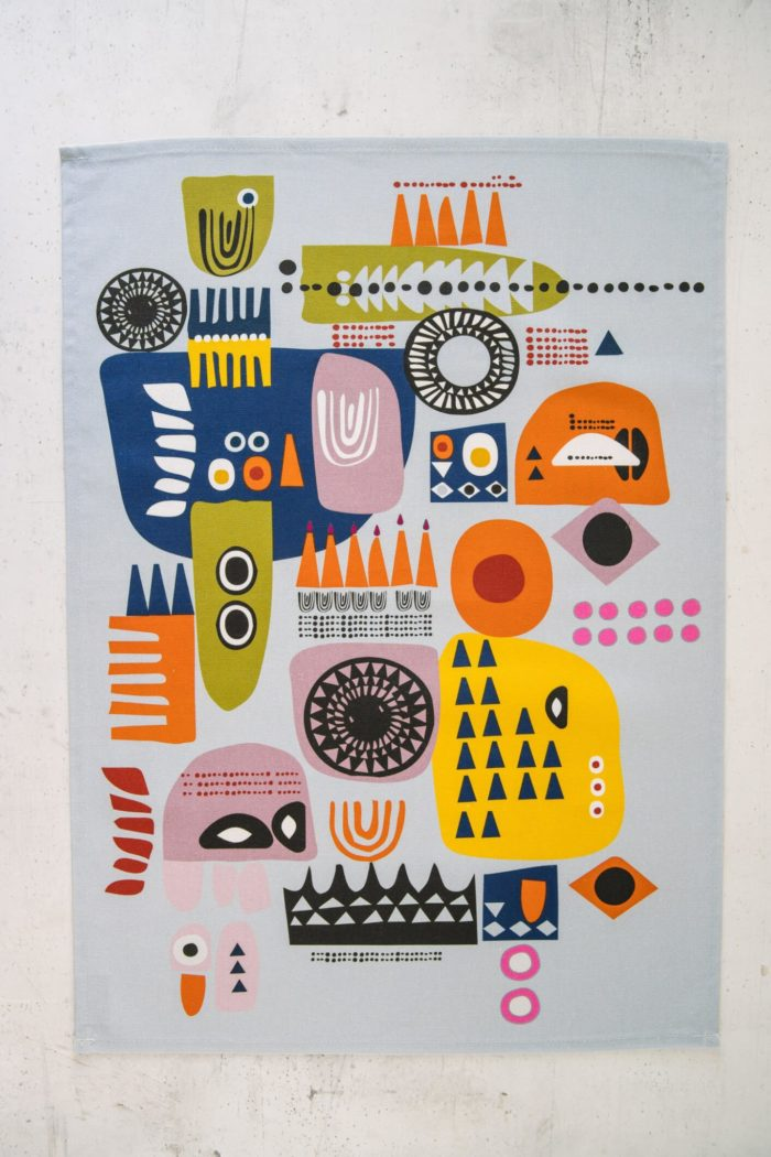 """The """"Shapes"""" colourful tea towels are a Scandinavian influenced abstract, bold and contemporary design. The two contemporary tea towel designs have subtle differences, both with playful, colourful combinations of abstract patterns suggesting faces. Design 1 (seen here) has more yellow, while design 2 has more blue. You can match or mix and match these quirky tea towels with oven gloves in the same design, for a full kitchen set. Features: Hanging loop 50cm x 70cm 100% cotton Wash at 40 degrees Made in Great Britain If you like this quirky design, you might also like to mix and match with the bright and bold """"Solstice"""" tea towels, oven gloves and apron for a full kitchen set. Both designs are strongly influenced by Scandinavian folklore and design. All dyes used by Softer + Wild are water-based and very gentle and reflect a rustic, organic feel to their products – perfect for gifting and bring comfort, luxury and design to the table."""