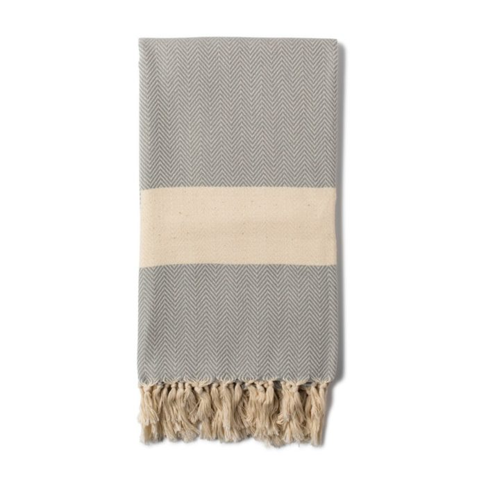 Ferah organic cotton towel is a Sky Blue or Dove Grey herringbone weave peshtemal towel with hand knotted tassels. Seen here in Dove Grey. Use as a towel, scarf, throw or sarong.