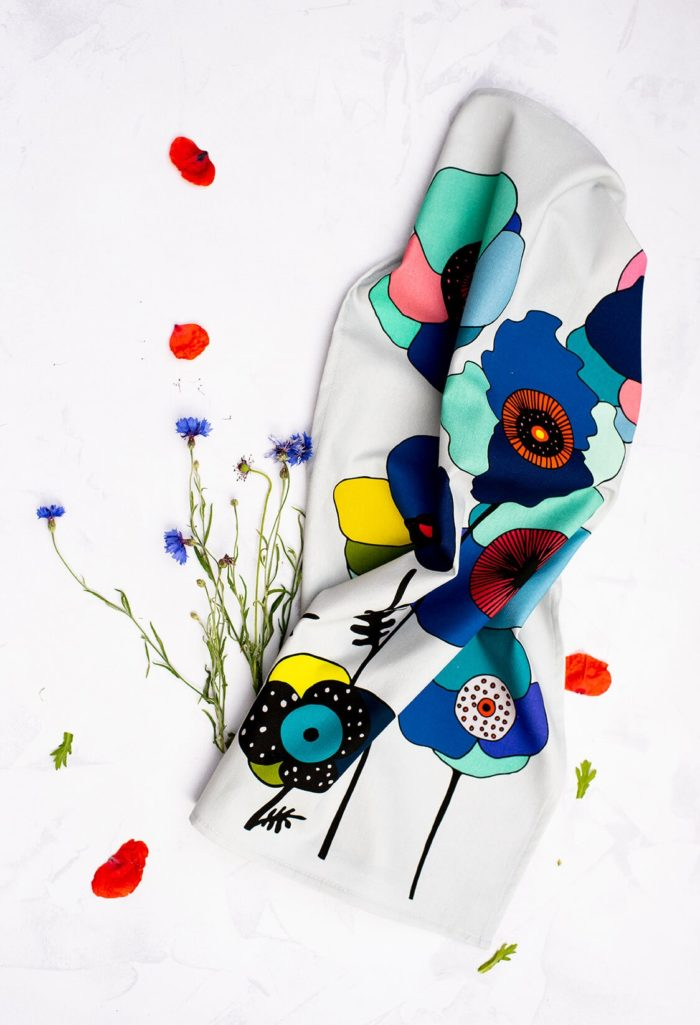 """Bright and colourful floral tea towel featuring hand-drawn summer flowers. This Poppy botanical tea towel comes in two bold designs, in red and blue. Choose from a repeated pattern (""""Pattern"""") or a single motif (""""Portrait""""). Seen here is Blue Portrait. The shapes and colours are evocative of fun retro designs from Scandinavia. 70 x 50cm"""