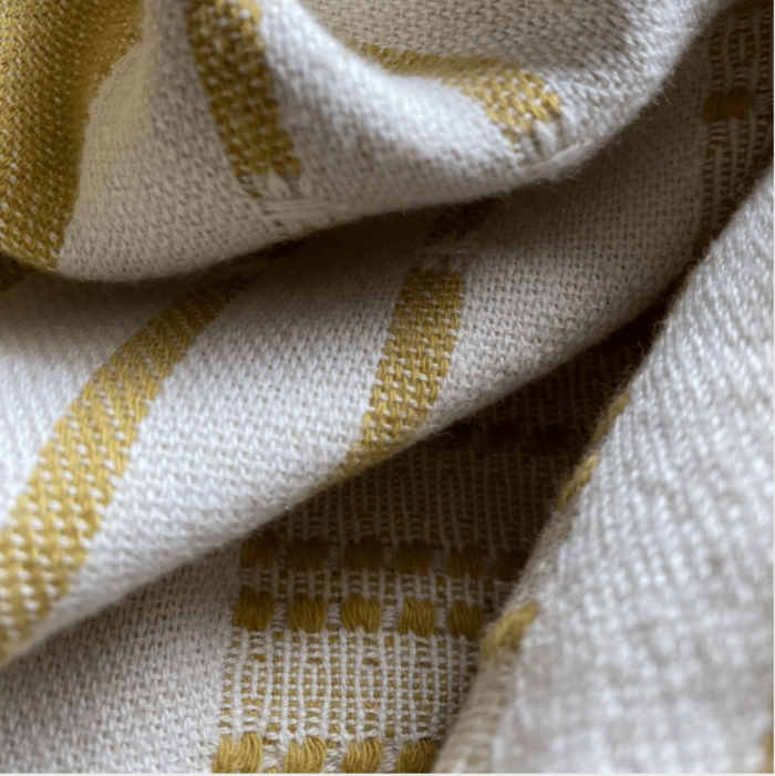Defne are super soft and sumptuous, jacquard loomed peshtemals in organic cotton, perfect for cooler seasons. 90 x 175 cm. Seen here in close up of the pickle colour.