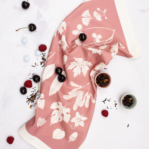 Pink tea towel with leaves and nuts, in a Scandinavian style. Designed and made in the UK. The natural cotton softens with use. 70 x 50cm